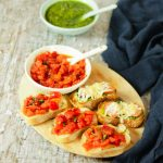 platter of bruschetta with tomato topping and bowl of pesto