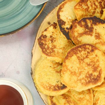 Cornmeal Pancakes on a plate with a cup of tea on the side