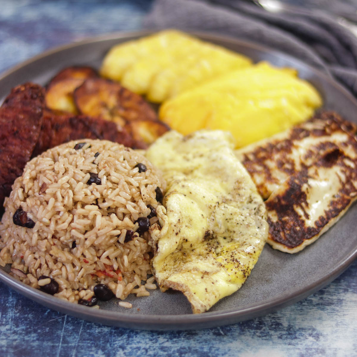 Gallo Pinto - Costa Rican Rice & Bean Breakfast Platter is a hearty and filling breakfast with rice and beans as the centerpiece, accompanied by eggs, cheese, chorizo, plantain, fruit and coffee.
