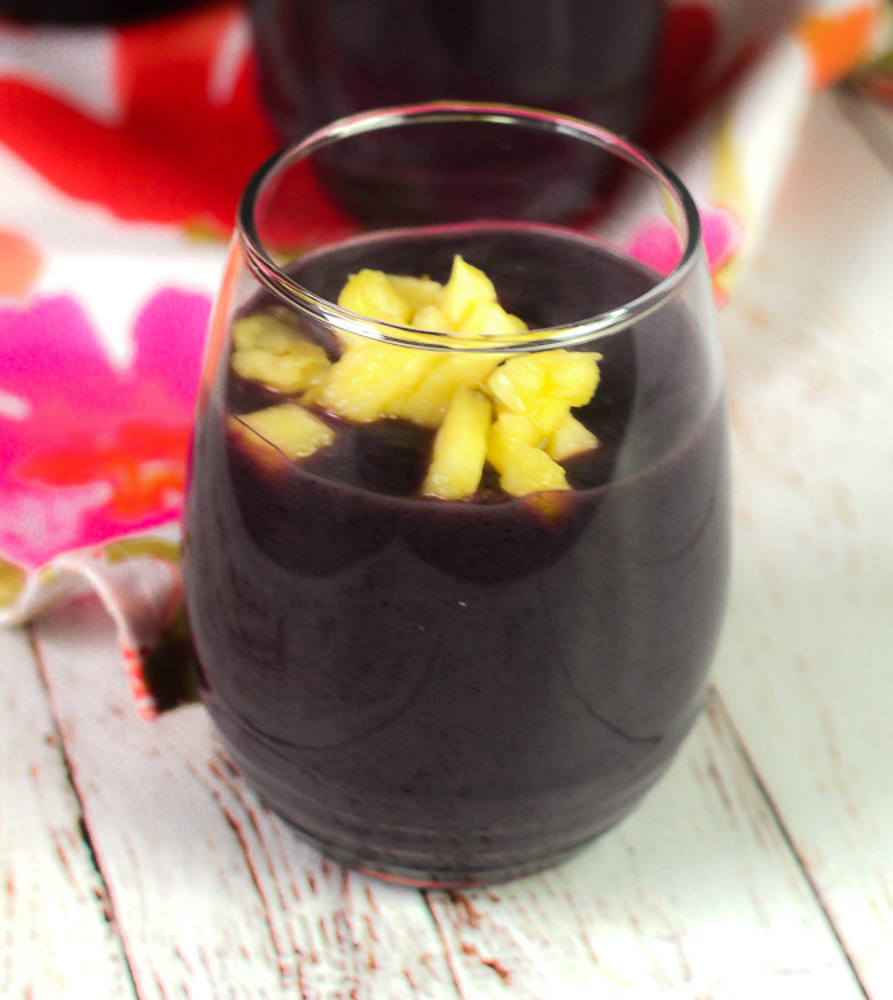 glass of blue cornmeal drink with chopped pineapple