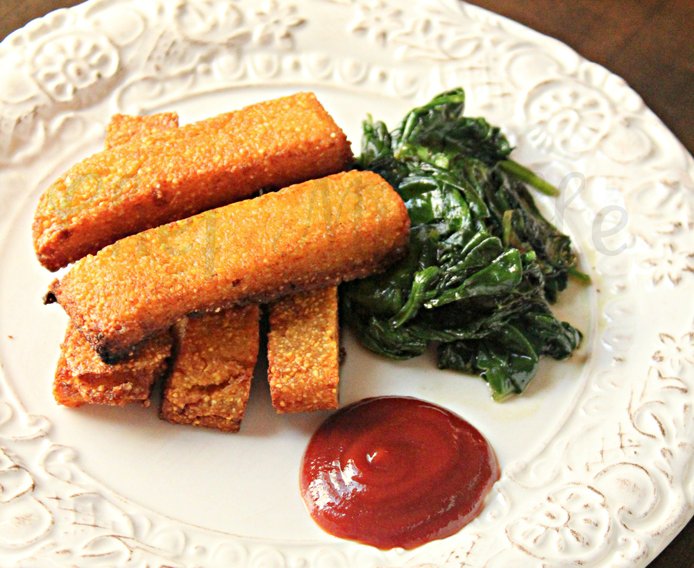 plate of polenta fries with ketchup and sauteed spinach