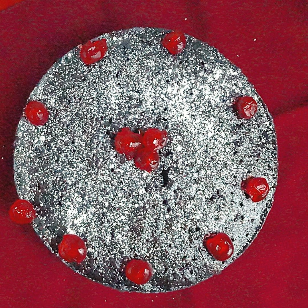 Caribbean Fruit Cake decorated with glace cherries and powdered sugar