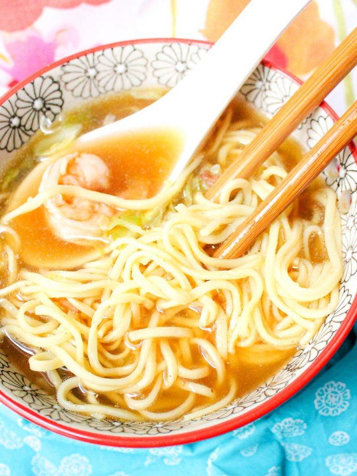 bowl of noodle soup with shrimp and chopsticks