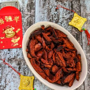 bowl of Char Sui Pork with Chinese New Year decorations