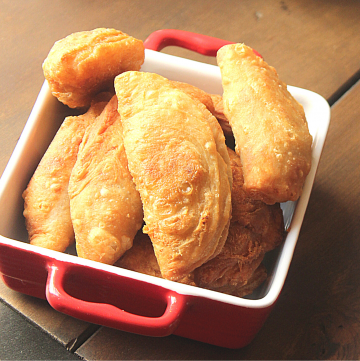 Aruba Style empanadas in a red square bowl on a wooden table