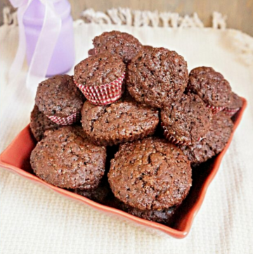 chocolate muffins in a square bowl on a tea towel