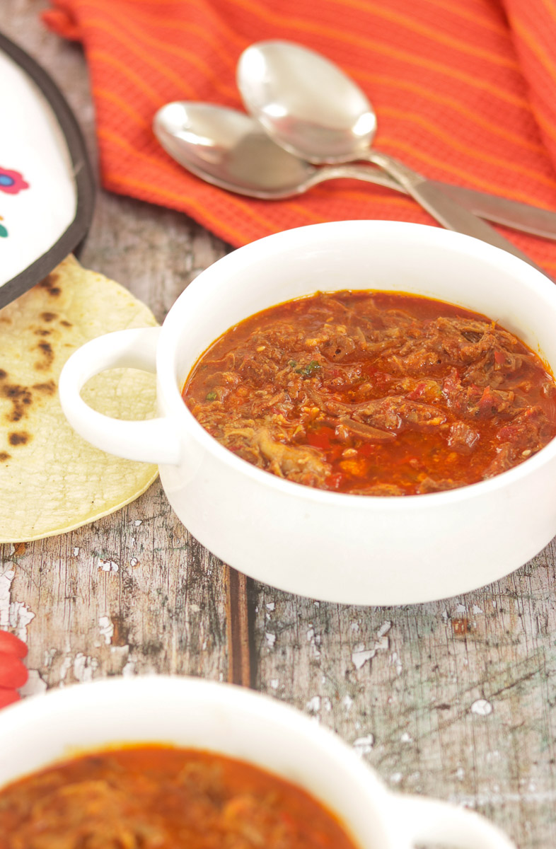 bowls of birria consome with spoons