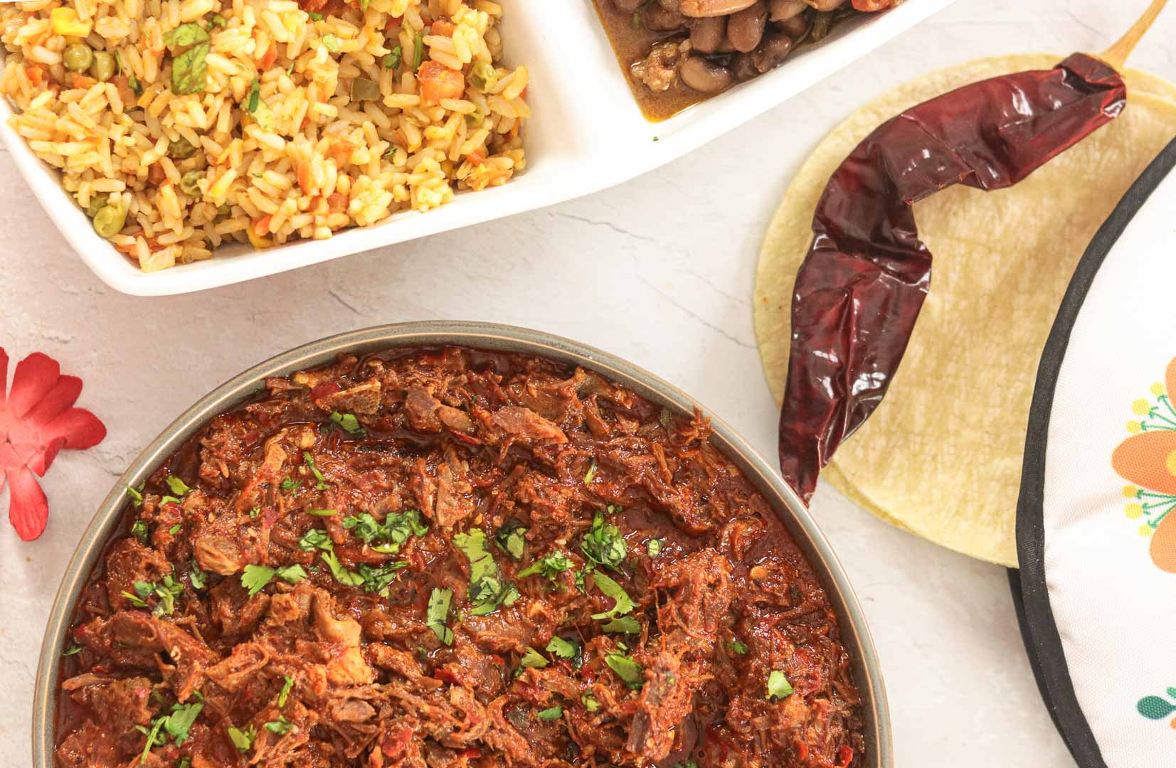 Birria with guajillo chillies and Mexican Rice in background.