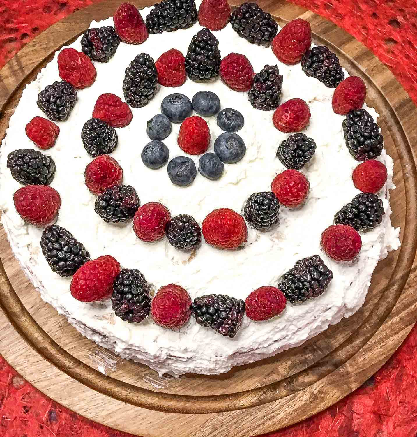 Cream Cake recipe with fresh berries and vanilla custard with whipped cream forsting.