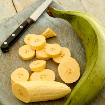 slices of plantain with a raw planain and a knife on a cutting board