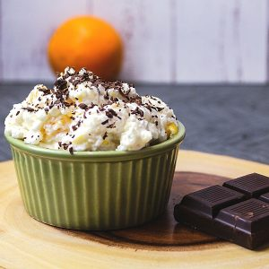 rice pudding in a bowl with text and an orange in the background
