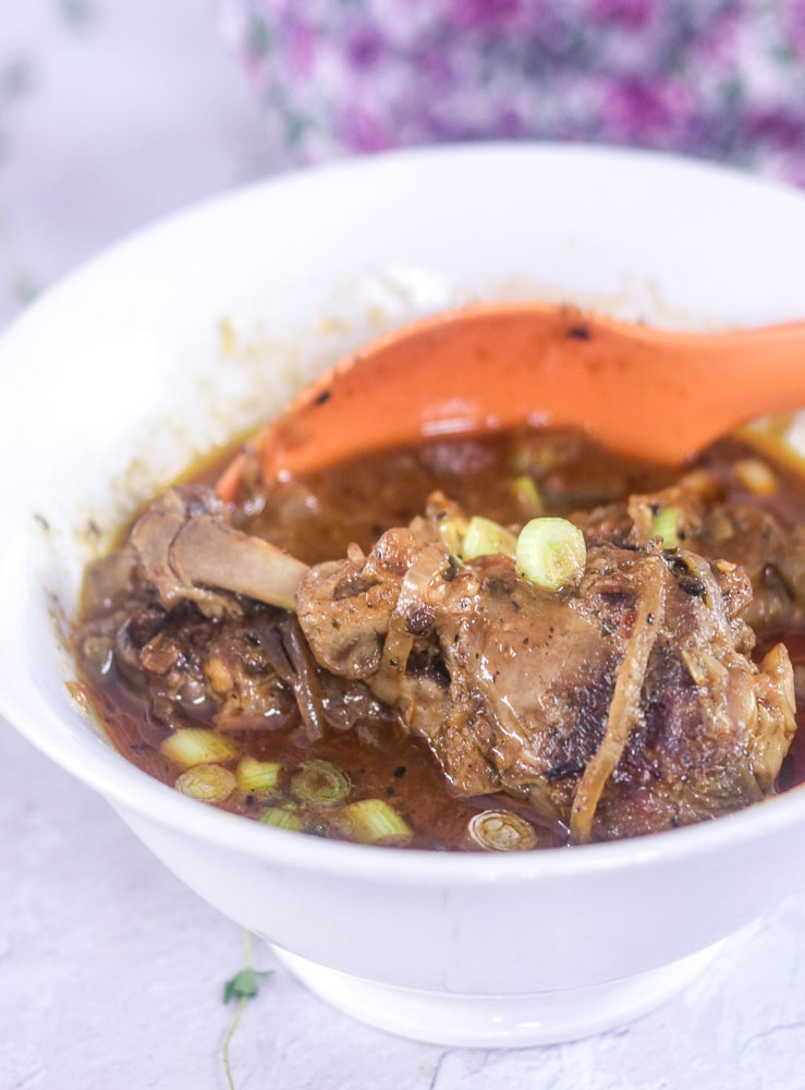 Haitian Stew Chicken with orange serving spoon in a bowl,