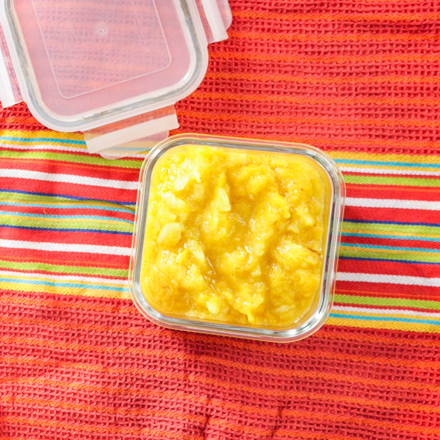 Mango Applesauce in a bowl on a bright colored kitchen towel.