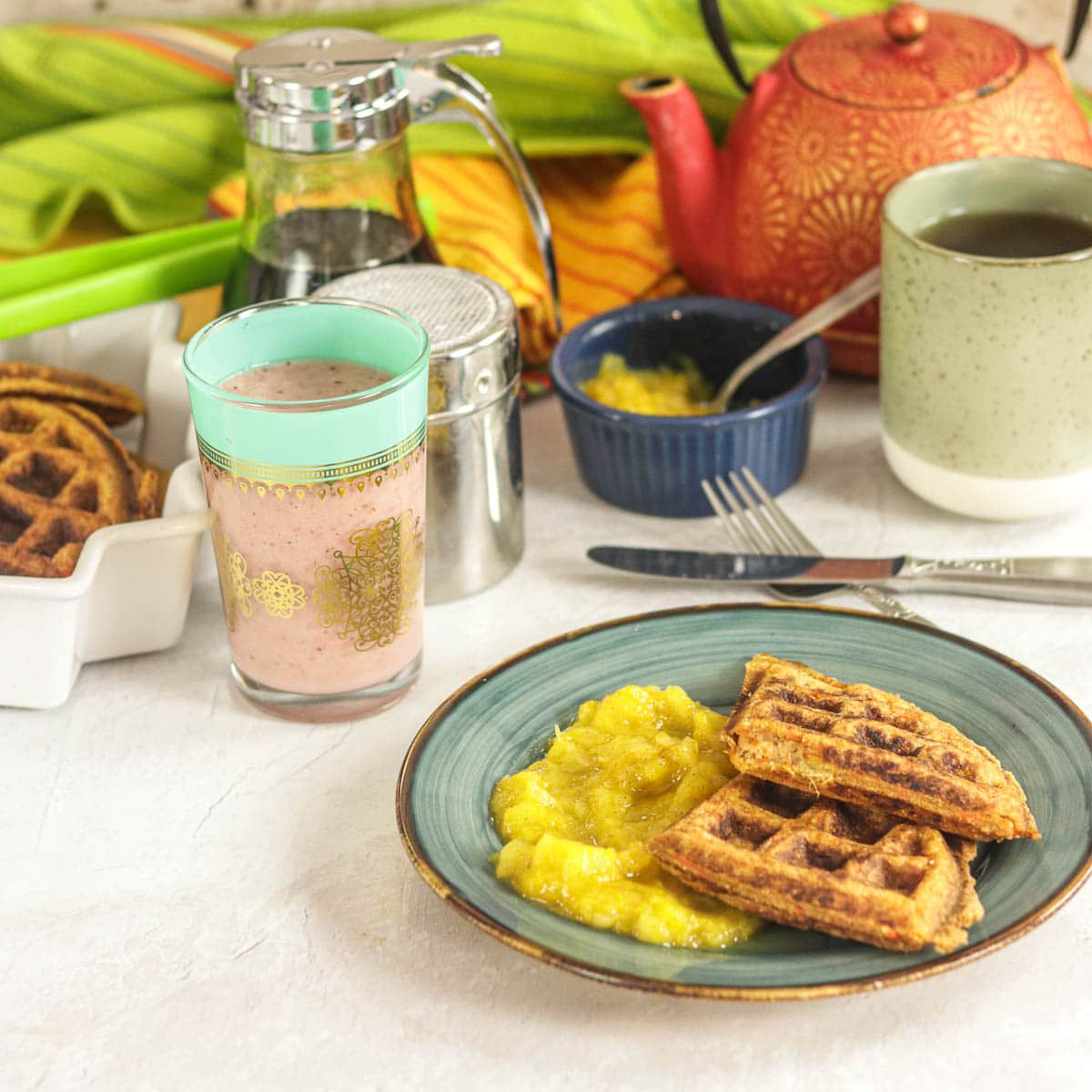 Healthy Whole Wheat Waffles with Mango Applesauce on a plate with breakfast accoutrements in the background.