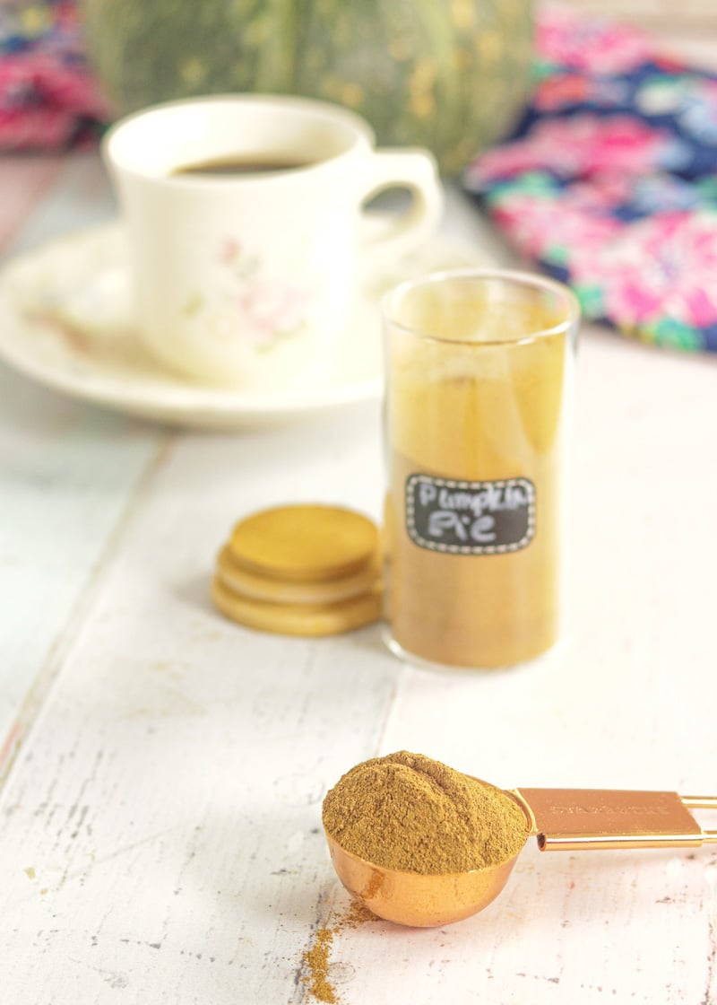 Pumpkin Spice Mix on a spoon with a jar and a cup of coffee in the background