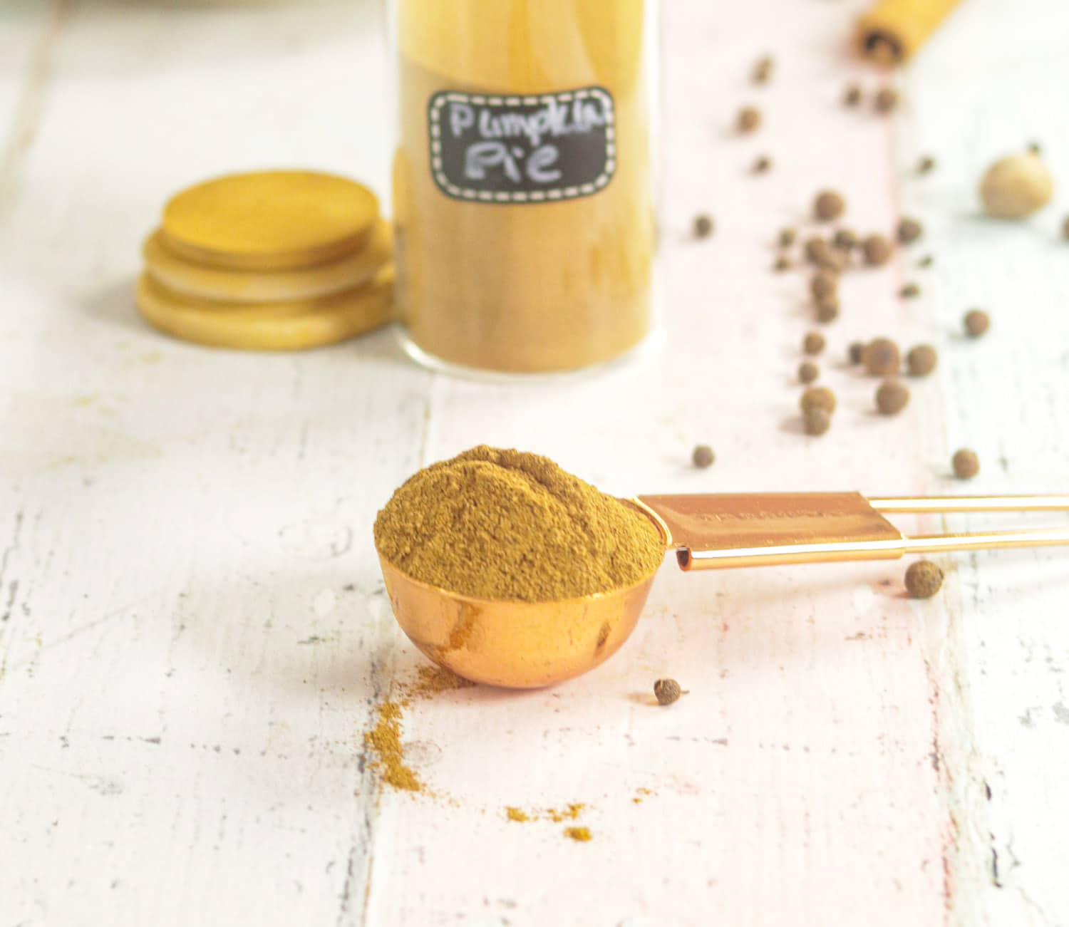 Pumpkin Pie Spice Mix on a spoon with whole spices in the background