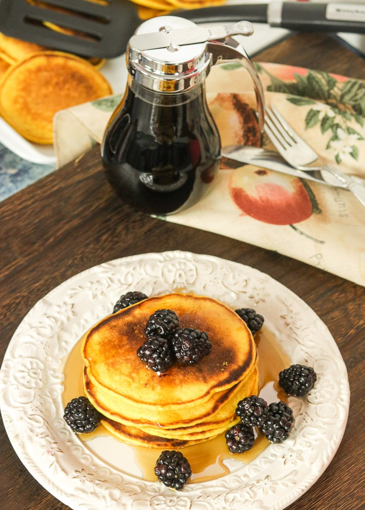 Pumpkin Pancakes on a plate with syrup and blackberries