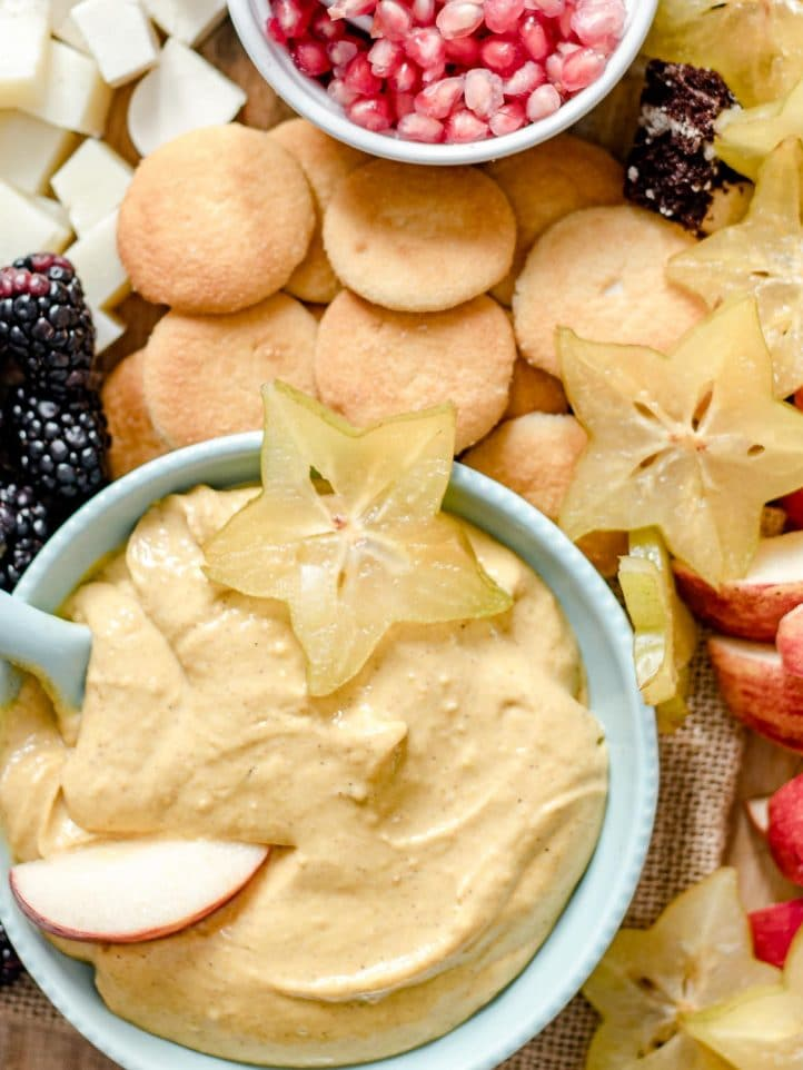 bowl of pumpkin dip with fresh fruit, cheese and cookies
