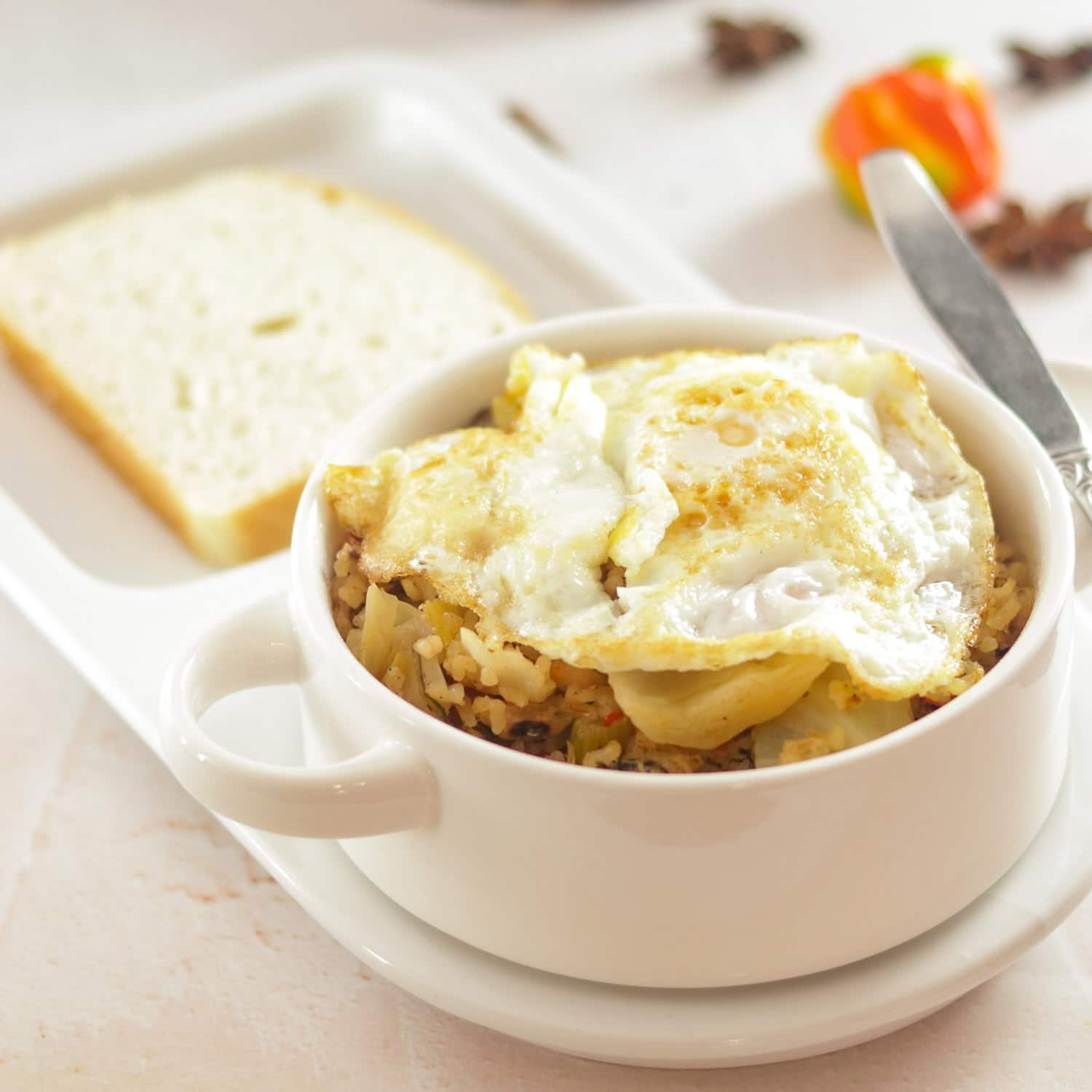 rice and chicken topped with a fried egg with a slice of bread in a bowl