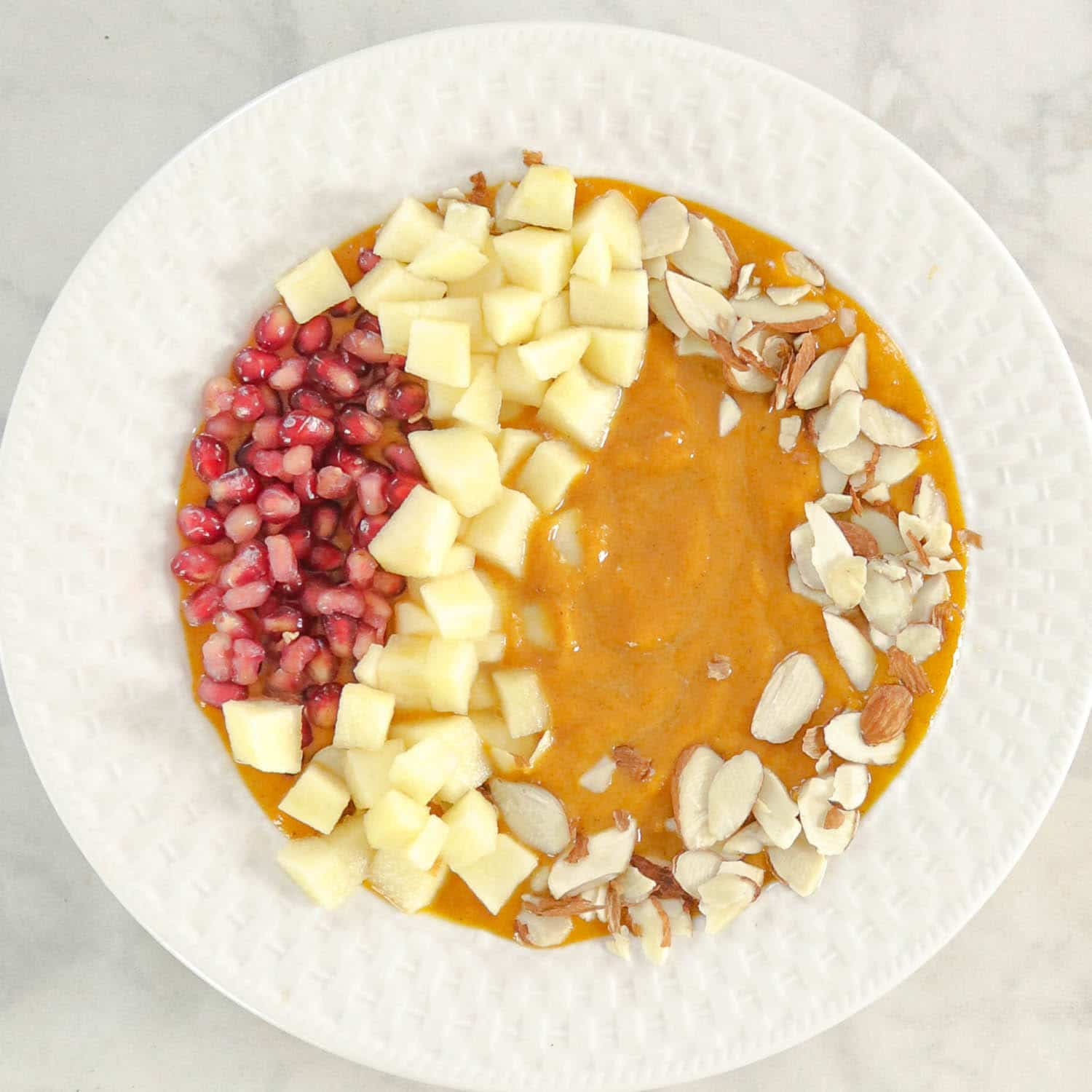 Pumpkin Smoothie in a bowl topped with fruits and nuts