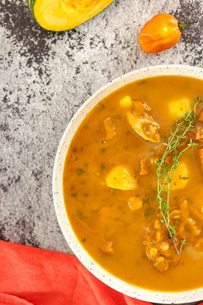 bowl of pumpkin soup garnished with fresh thyme