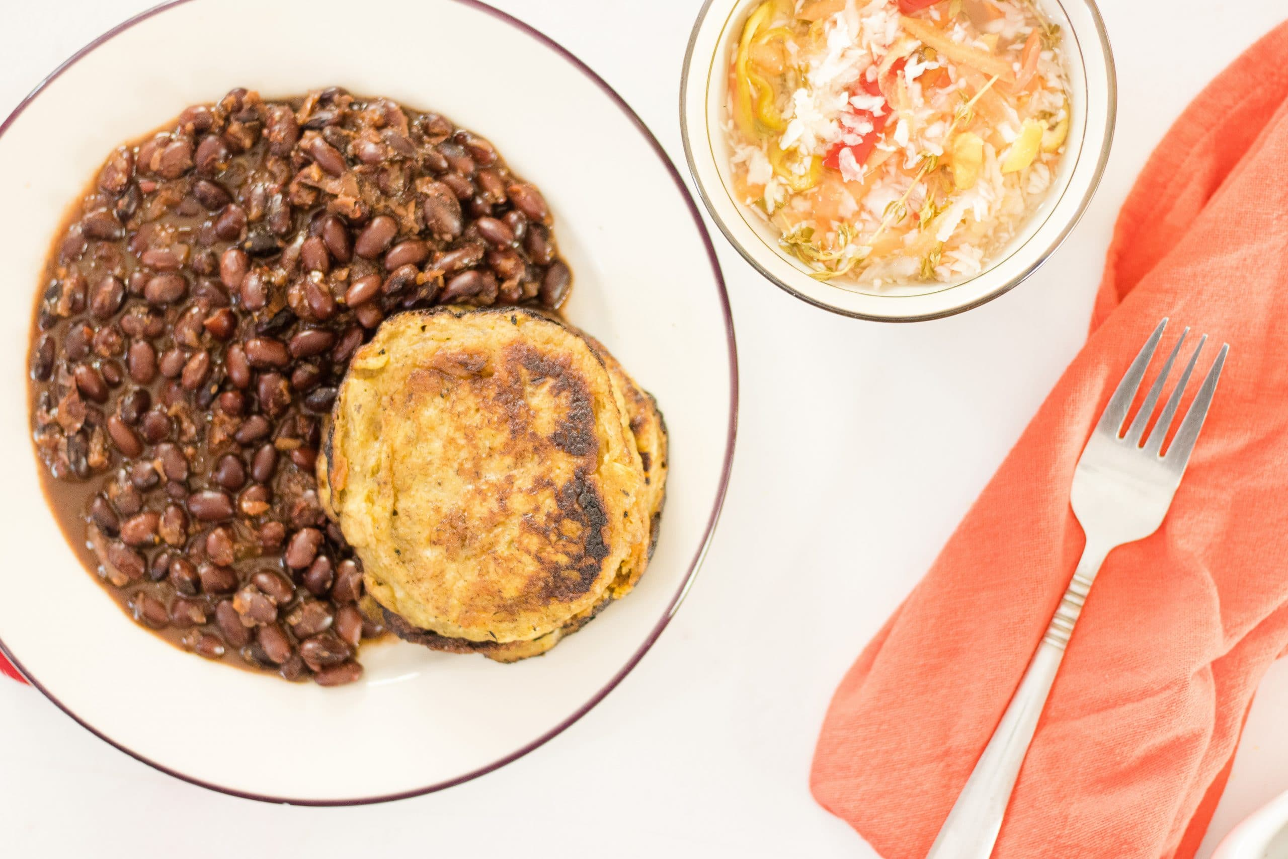 Tatale Plantain Pancakes on a plate with beans and pikliz in a bowl.