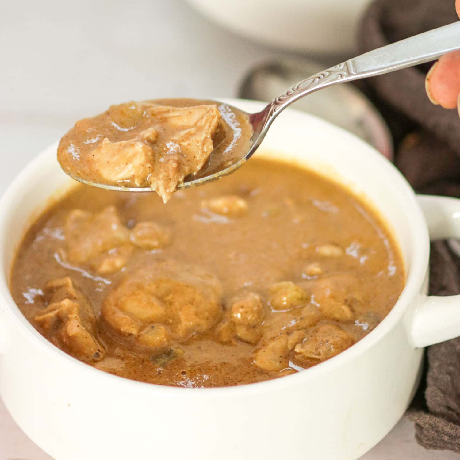 Suriname Style Peanut Soup in a bowl with a spoon